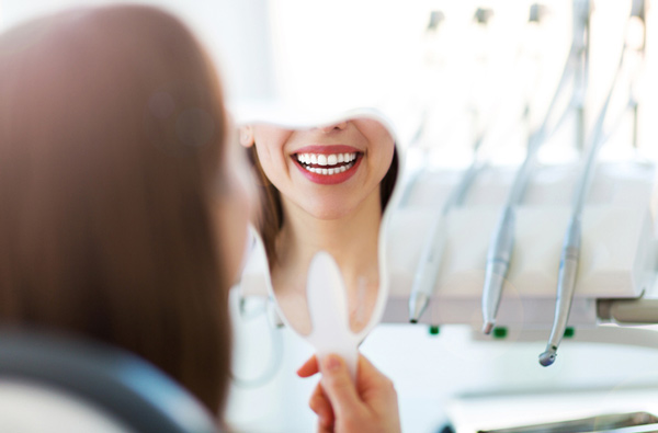 Woman looking at her smile in a mirror after restorative dental services from Lincoln Center Smiles